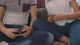 Close up shot of man playing video game while woman using smart phone.