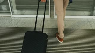 Close up shot of man with the baggage walking to the modern airport terminal. Dolly shot.