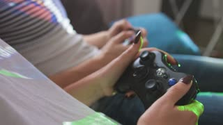Close up shot of woman and man hands who playing video game while sitting on sofa. Side view.