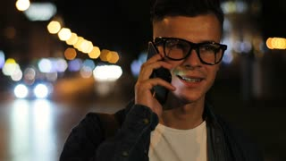 Close up shot of young emotional man talking on the smart phone in the city at the night. Side view.