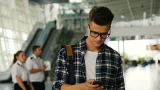 Close up shot of young man in the glasses walking in the modern airport terminal and talking on smart phone with friends.