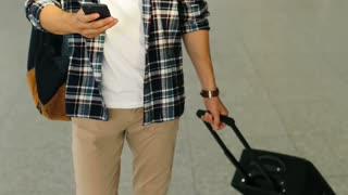 Close up shot of young man with the baggage walking in the modern airport terminal and using smart phone for chatting with friends.