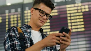 Close up shot of young smiling man with glasses using smart phone for checking his flight on the arrivals table background.