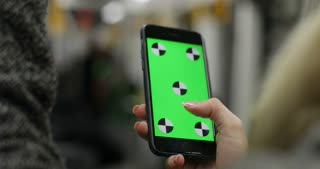 Close-up view of woman hand holding a smartphone with pre-keyed green screen, in public transport. Girl surf the Internet with touchscreen.