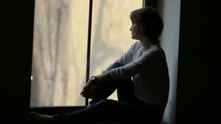 Confident woman in casual wear sitting near window looking out