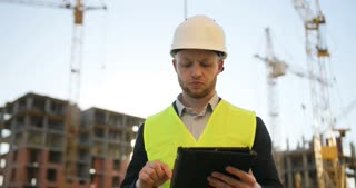 Construction engineer in white helmet and green vest at the construction site using the tablet for work. Outdoor.