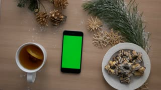Cozy Christmas top view. Smartphone with green screen on wooden table. Christmas decoration, biscuits, tea. Chroma key