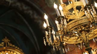 Dolly shot of beautiful luxury chandelier with lamps in the church.