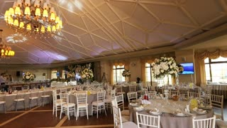 Dolly shot of decorated white stylish tables for the guests and hall on a wedding day.
