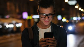 Emotional man in the stylish glasses using smart phone in the street at the evening time on road background.