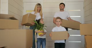 Family moving to a new home. Young exaciting family carrying cardboard box into the new modern home to the living room. Happy family with cardboard boxes in new house