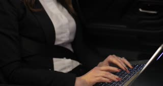 Female entrepreneur working with laptop computer in the backseat of car