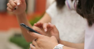 Female hands using the cell phone. One of the girls is wearing a watch. Outdoors.