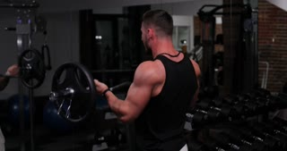 Fit man in sportswear lifting heavy weights during a workout session in a gym. Man exercising hardly with sport equipment in a gym. Sports and fitness concept