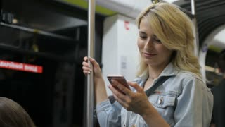 Girl typing message and browsing on mobile phone in public transport. City lights background while travelling on the public transport