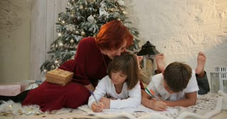 Grandmother and children near decorated christmas tree writing christmas letter to Santa Claus. The morning before Xmas. Family with kids celebrating Christmas at home