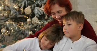 Grandmother hugging her grandkids near decorated christmas tree. The morning before Xmas. Family with kids celebrating Christmas at home