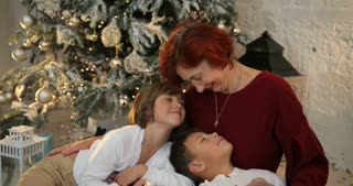 Grandmother hugging her grandkids near decorated christmas tree. The morning before Xmas. Family with kids celebrating. Christmas holiday and New Year.