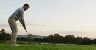 Handsome Caucasian golf player getting ready and hitting a ball with a club on a summer weather day. Outdoor. Golf field.