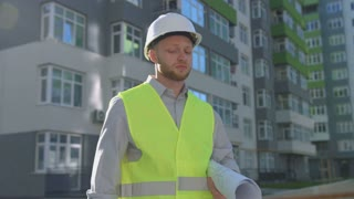 Handsome caucasian worker in white helmet and green vest talking on mobile phone while standing near built house.