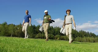 Handsome male golf players walking with their golf bags on the golf pitch to play a game. Outside. Sunny summer day.