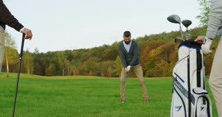 Handsome man with beard playing golf on the pitch. Golf bag and club on the first plan. Outside