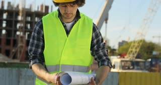 Handsome young builder in yellow helmet on unfinished construction background. Architect analysing drawing and looking in side. Outdoor.