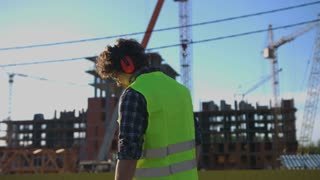Handsome young builder with black curly hair in protected glasses and headphones looking around on unfinished construction background.