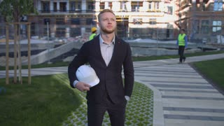 Handsome young business man with rousse hair and beard in suit and shirt standing on unfinished construction background, taking on head protected helmet. Outdoor.