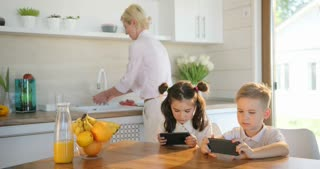Happy family home, little sister and brother using mobile phone together. Mom with kids laughing watching funny video.