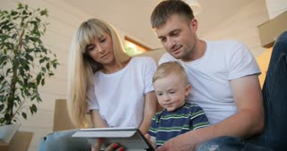 Happy family portrait with tablet pc computer. Husband and wife and their son moving in new home. Mortgage, people, housing and real estate concept.