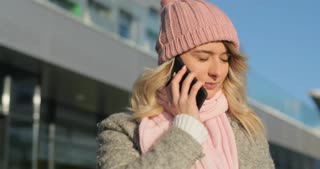 Happy girl answering call, talking on the smart phone. Woman Wearing A Winter Coat And Pink Scarf and hat. Modern building background