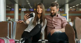 Happy young beatiful loving couple is sitting and making selfie at airport lounge.