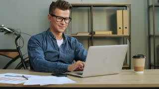 Happy young business man in the glasses working in the modern office, using laptop.