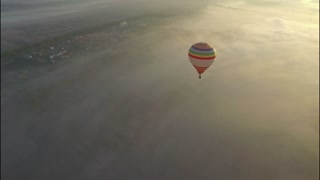 Hot air balloon floating in the pure blue sky on the sunrise above the city