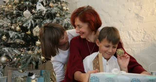 Kids and grandmother opening Xmas presents. Children under Christmas tree with gift boxes. Family with kids celebrating. Girl hugging her grandmother