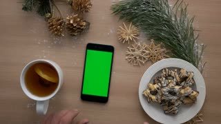 Male hands using mobile phone with green screen, scrolling pages. Christmas decoration background. Chroma key. Close up. Top view