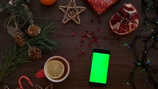 Man finger tapping on a smart phone touchscreen with green screen. Christmas decor on the wooden table background. Chroma key. Top view, Shot from above