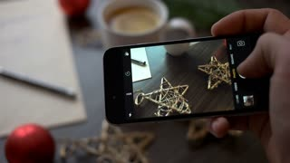 Man hands taking beautiful picture on the smart phone. Christmas, New Year. Close up man hands taking cozy chrismas photo