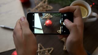 Man hands taking the photo on smart phone of christmas decoration on brown wood background. Christmas photo on smart phone.