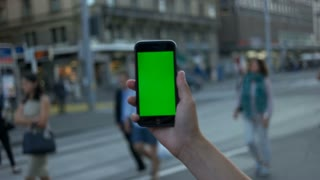 Mans and holding a smart phone with green screen on train station background with people. Close up. Chroma key.