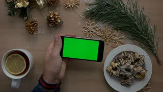 Mans hand using smart phone with green screen on light wood background with Christmas decoration . Top view. Chroma key. Horizontal position.