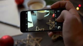 Mans hands taking cozy christmas pictures on smart phone. Man taking photo of christmas decor on the table on his phone. Close up