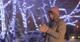 Outdoor close up portrait of a young woman in pink warm clothes trying to warm herself in night winter city. Winter concept. Christmas, winter holidays concept. Snowfall.
