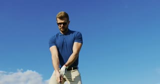 Portrait of a handsome Caucasian man in glasses playing golf and making a hit with a club. Nice sunny weather and blue sky background. Outside.