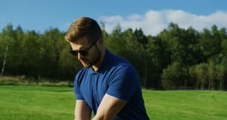 Portrait of a handsome Caucasian man in glasses playing golf. Golf player making a hit with a club. Nice sunny weather. Outside. Close up.