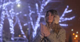 Portrait of a young woman wearing ear muffs with head tilted, trying to warm herself in night winter city. Winter concept. Christmas, winter holidays concept. Snowfall.