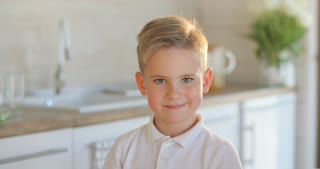 Portrait of adorable young happy boy looking at camera. Isolated on the white kitchen background. Little boy smiles and looking forward. Young people and emotion