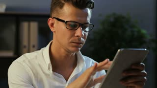 Portrait of attractive man in office using electronic tablet for working at the evening time.