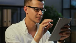 Portrait of attractive man with glasses in office using electronic tablet for working at the evening time.